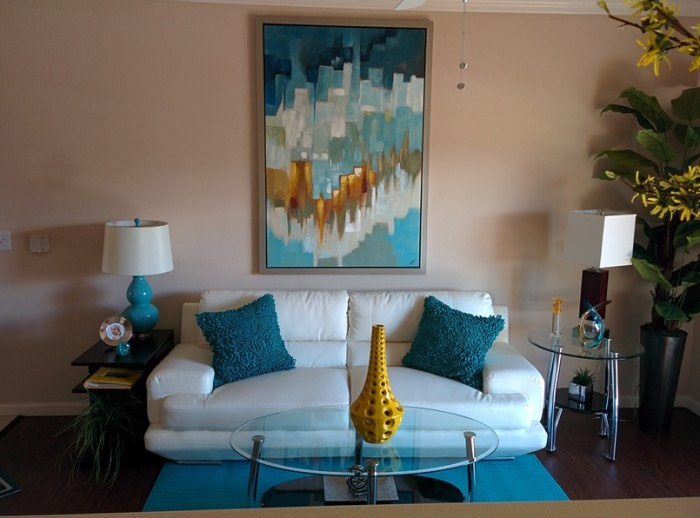 White couch with blue fluffy pillows and contemporary colorful blue and gold painting above